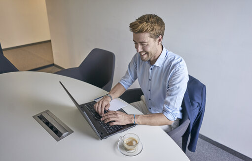 Smiling businessman working on laptop in board room - BEF00074