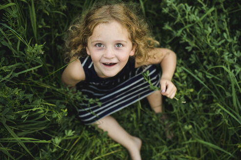 Girl looking up at camera on green grassy field - CUF09991