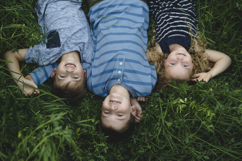 Brothers and sister enjoying outdoors on green grassy field - CUF09994