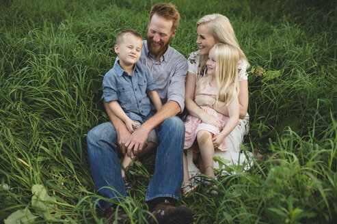 Family sitting in tall grass together smiling - CUF10078