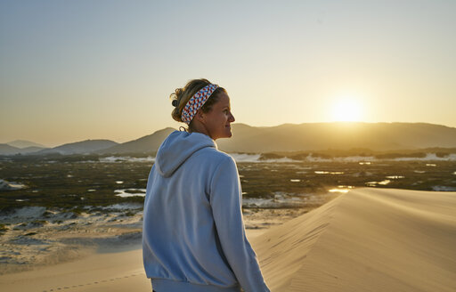Woman looking away at sunset over dunes, Florianopolis, Santa Catarina, Brazil, South America - CUF10186
