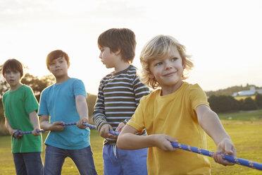 Team of four boys preparing for tug o'war on playing field - CUF10336