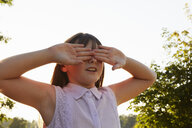 Girl covering eyes for hide and seek in park - CUF10339
