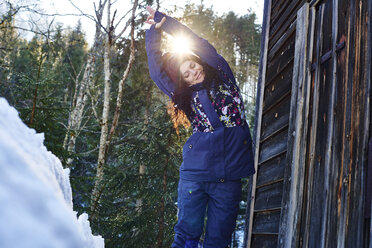 Woman in winter clothes practicing half moon yoga pose in snow by log cabin, Austria - CUF10372