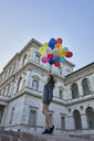 Germany, Munich, happy young woman with bunch of balloons - BEF00080