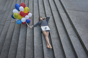 Young woman with bunch of balloons, laptop and smartphone lying on stairs listening music with headphones - BEF00083