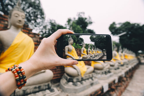Thailand, Ayutthaya, Wat Yai Chai Mongkhon, taking a photo from Buddha with smartphone - GEMF01991