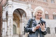 Mature woman looking at smartphone in city, Siena, Tuscany, Italy - CUF10418