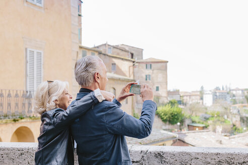 Tourist couple photographing cityscape, Siena, Tuscany, Italy - CUF10421