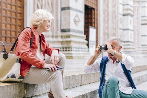 Senior male tourist photographing wife on Siena cathedral stairway, Tuscany, Italy - CUF10424