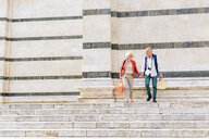 Tourist couple moving down Siena cathedral stairway, Tuscany, Italy - CUF10427