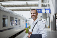 Mature man standing on station platform, holding healthy juice drink - CUF10439