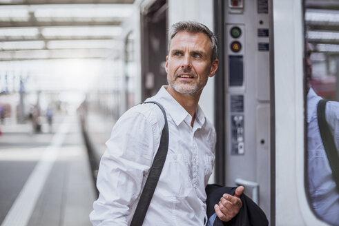 Mature man on station platform, boarding train - CUF10442