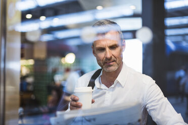 Mature man sitting in cafe, reading magazine, holding takeaway coffee cup - CUF10445