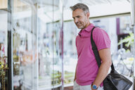 Mature man looking in shop window - CUF10451