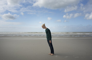 Boy standing on beach,leaning forward in the stormy wind, Gravelines, Nord-Pas-de-Calais, France - CUF10472