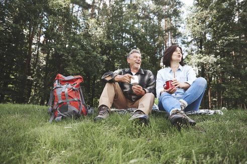 Mature couple relaxing on grass, holding tin cups, rucksack beside them - CUF10538