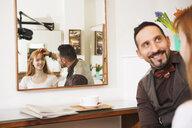 Male hairdresser advising customer on hairstyle in salon - CUF10551