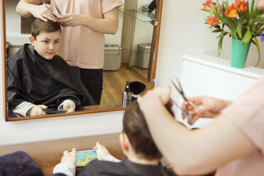 Male hairdresser trimming boy's hair in hair salon - CUF10557