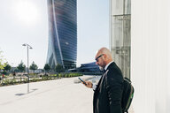 Mature businessman standing outdoors, using smartphone - CUF10575