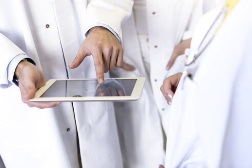 Mid section of male and female doctors using digital pad touchscreen in hospital - CUF10584