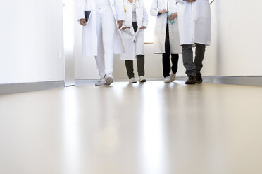Neck down view of male and female doctors walking in hospital corridor - CUF10587