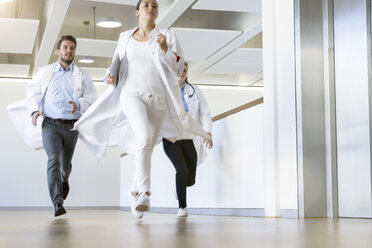 Male and female doctors running along hospital corridor - CUF10590