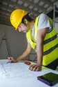 Worker looking at construction plan - KIJF01926