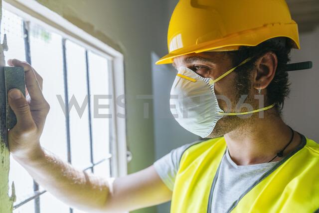 Close-up of worker sanding wooden window - KIJF01929