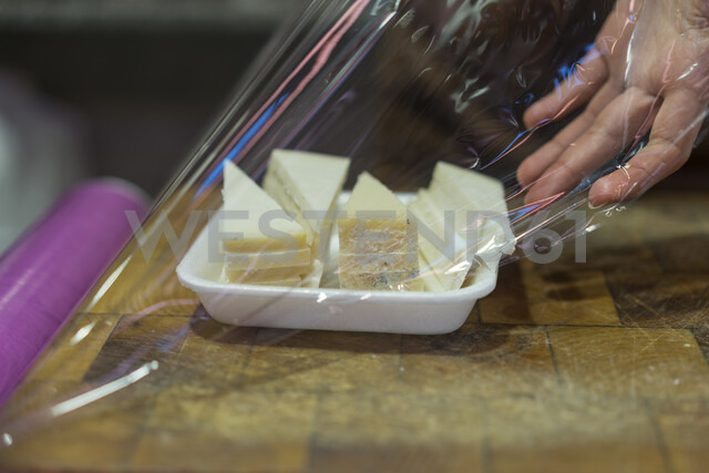 Saleswoman packing cheese in bowl with clingfilm - AFVF00457