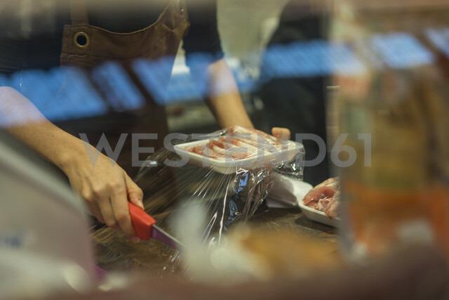 Female butcher cutting clingfilm - AFVF00460