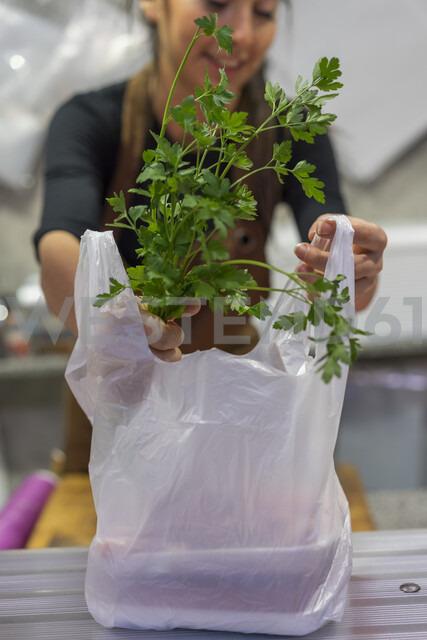 Female butcher giving plastic bag - AFVF00466