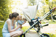 Mother and daughter playing by pram in park - CUF10716