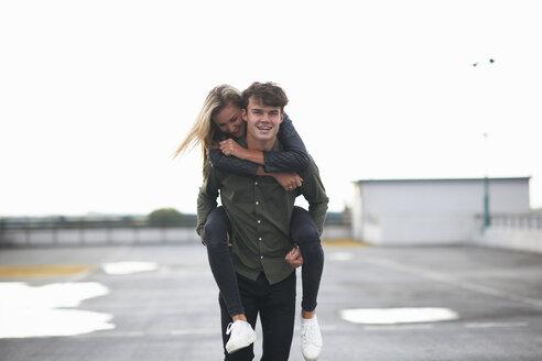 Young man giving girlfriend a piggyback across car park - CUF10731
