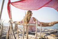 Rear view of woman sitting on beach relaxing, Palma de Mallorca, Islas Baleares, Spain, Europe - CUF10737