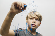 Close up of boy's hand writing equation onto glass wall - CUF10743