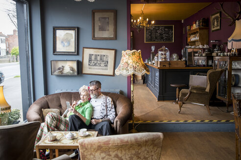 Quirky vintage couple looking at smartphone in tea rooms - CUF10779