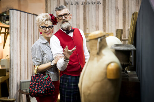 Quirky vintage couple shopping in antiques emporium - CUF10791