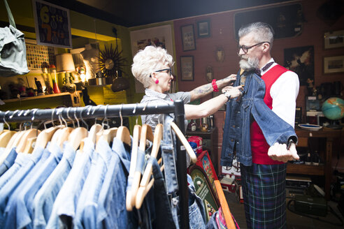 Quirky vintage couple shopping in vintage and antique emporium - CUF10794