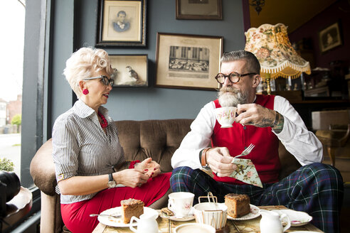 Quirky vintage couple drinking tea in tea room - CUF10797