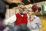 Quirky vintage couple laughing and looking at each other in antique emporium - CUF10806