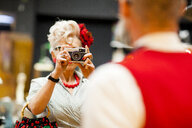 Quirky vintage woman photographing boyfriend on vintage camera in antiques emporium - CUF10809