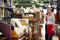 Quirky vintage couple shopping together in antiques emporium - CUF10812