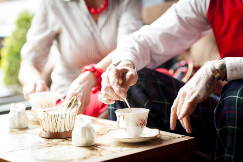 Close up of hands of senior man stirring tea in vintage tea rooms - CUF10815