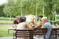 Three generation family having lunch on patio table - CUF10860