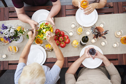 Overhead view of family handing salads at family lunch on patio - CUF10863