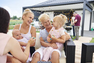 Three generation women with children on laps at family lunch on patio - CUF10866
