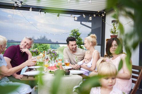 Three generation family having lunch on patio - CUF10872