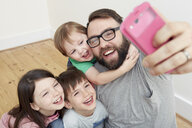 Mid adult man and three children taking smartphone selfie - CUF10896
