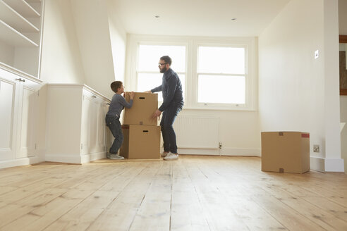 Mid adult man and son stacking cardboard box in new home - CUF10911